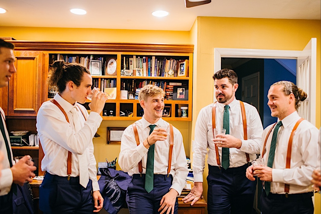 groom and groomsmen wear white shirts, blue trousers, and brown suspenders drink Chattanooga Whiskey