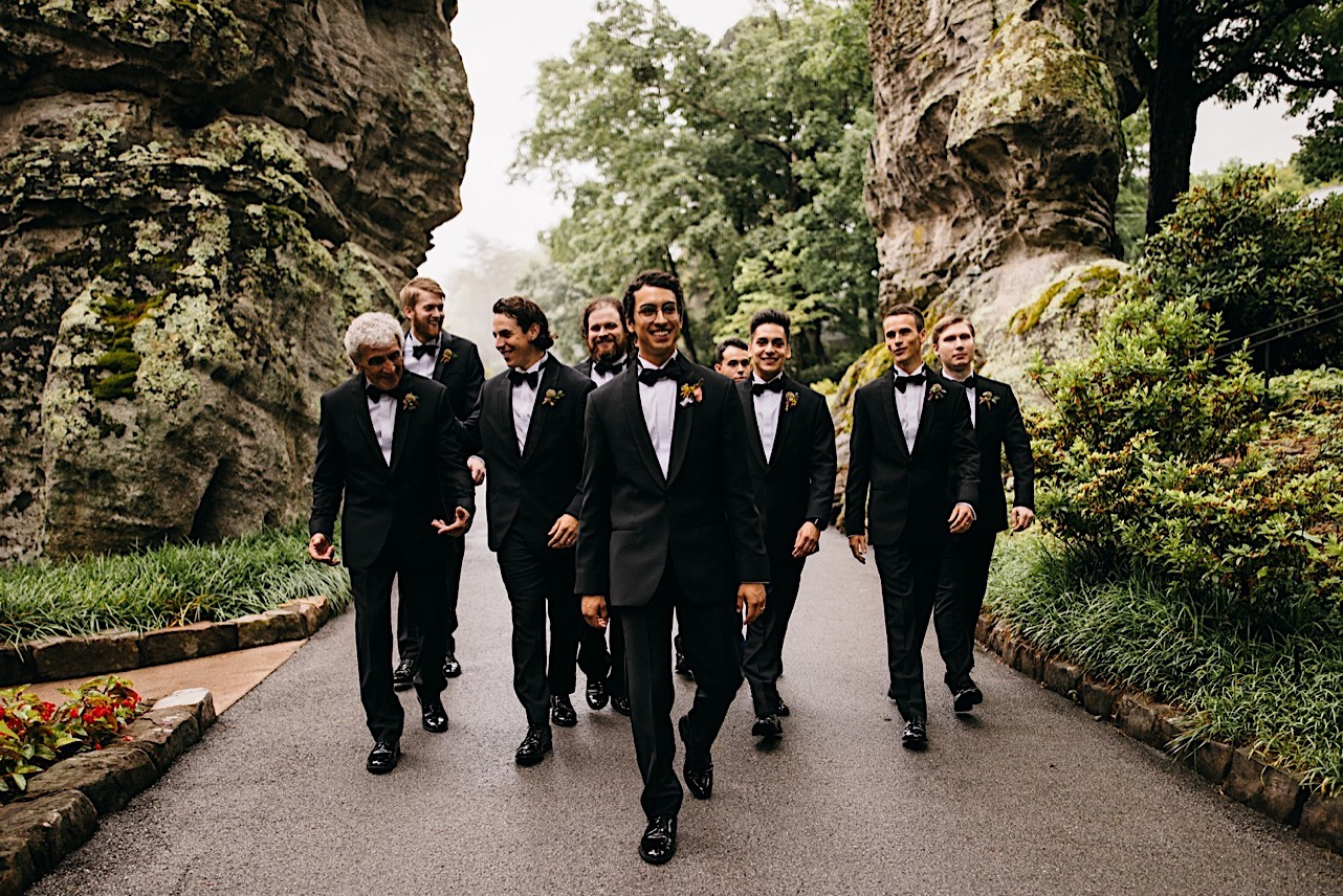 groom and groomsmen wear classic tuxedos and walk between huge rocks at Lookout Mountain Club