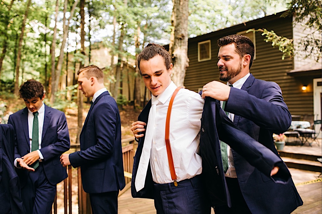 groomsman helps groom into his blue sport coat over his white shirt and tie