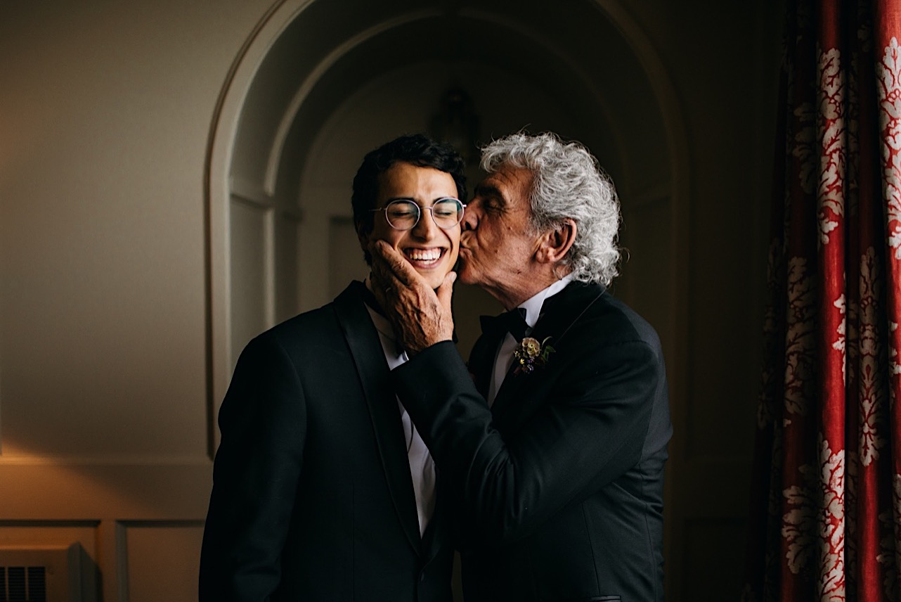 older groomsman kisses groom on his cheek while groom smiles widely