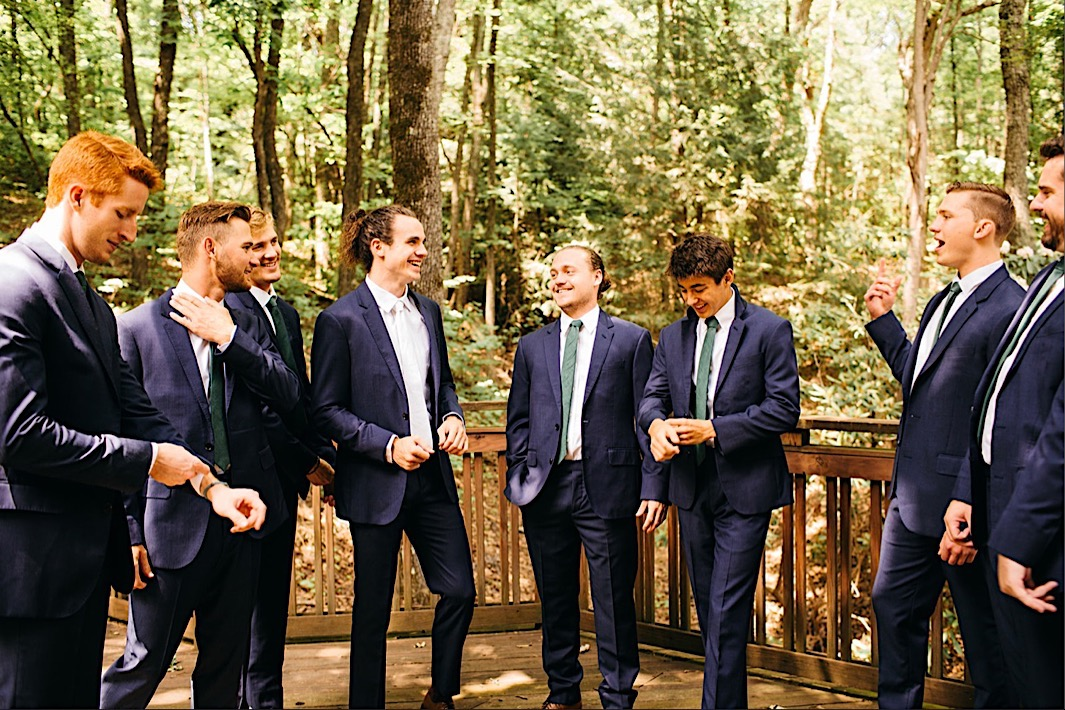 groom and groomsmen in blue suits laugh and talk on a deck in the woods