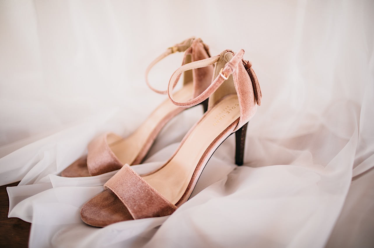 pink velvet high heels with ankle strap sitting on white fabric