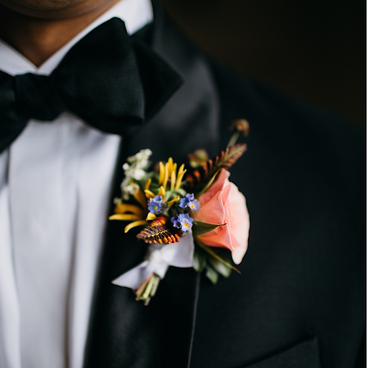 grooms Emily Kaye Designs boutonniere with small peach flower, purple, yellow, and white flowers