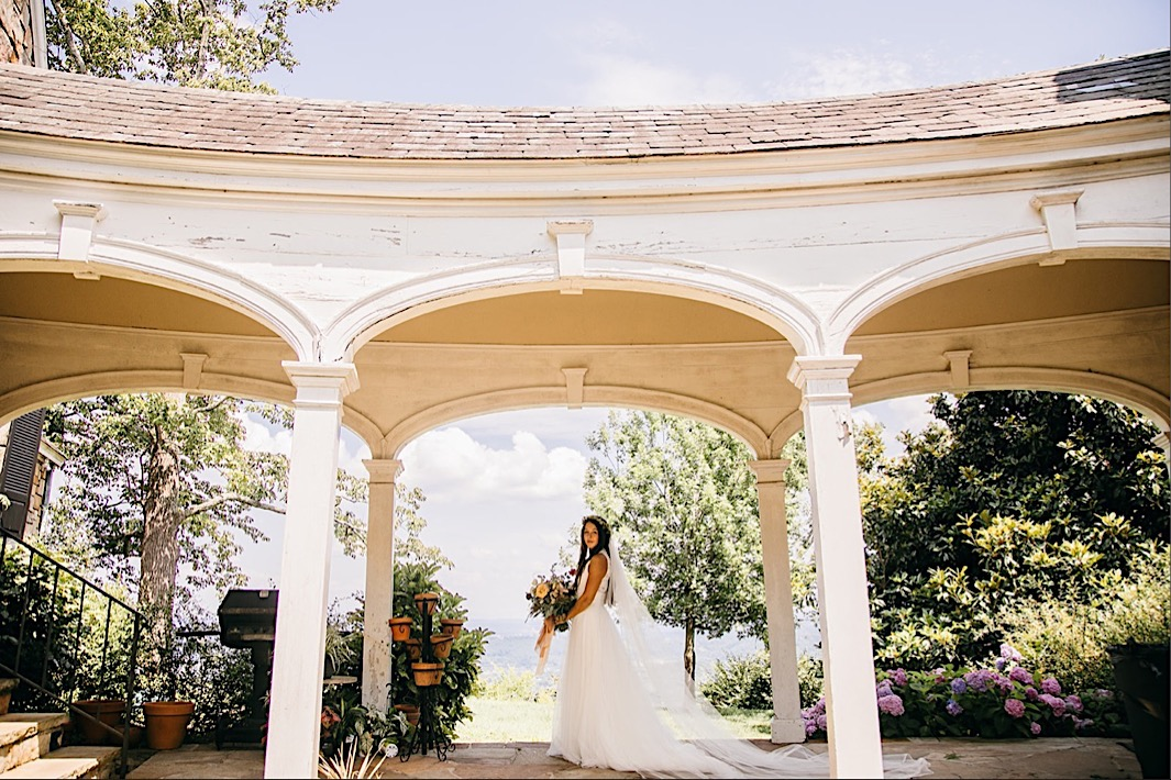 bride holds her Southerly Flower Farm bouquet under a wide, arched porch