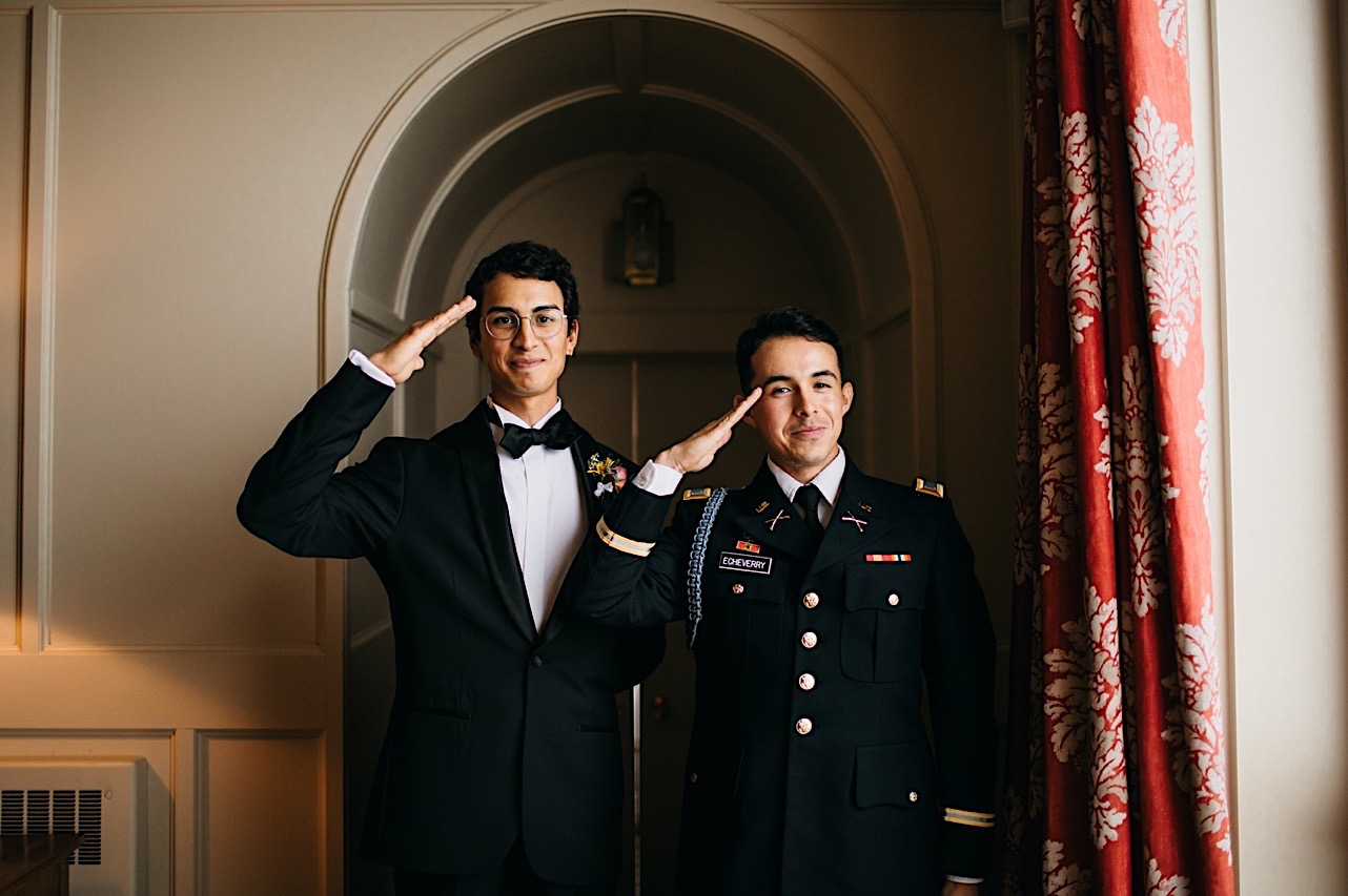 groom and best man stand in arched doorway and salute the camera in dark suits