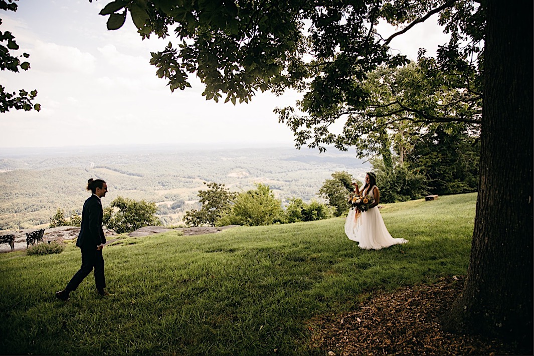 bride and groom walk toward each other across a grassy yard overlooking the Tennessee Valley