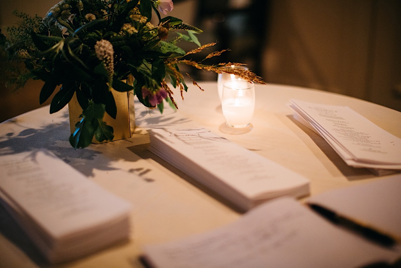 folded wedding programs sit on a white table beneath a vase of greenery and wild flowers