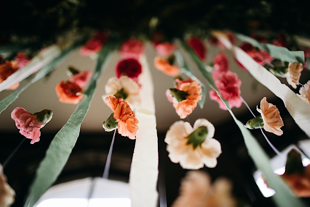 Emily Kaye Designs floral installation hangs flower blooms and streamers in front of large window at Lookout Mountain Club