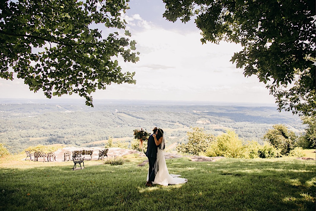 bride and groom hug under the shade of a tree on a bluff overlooking the Tennessee Valley