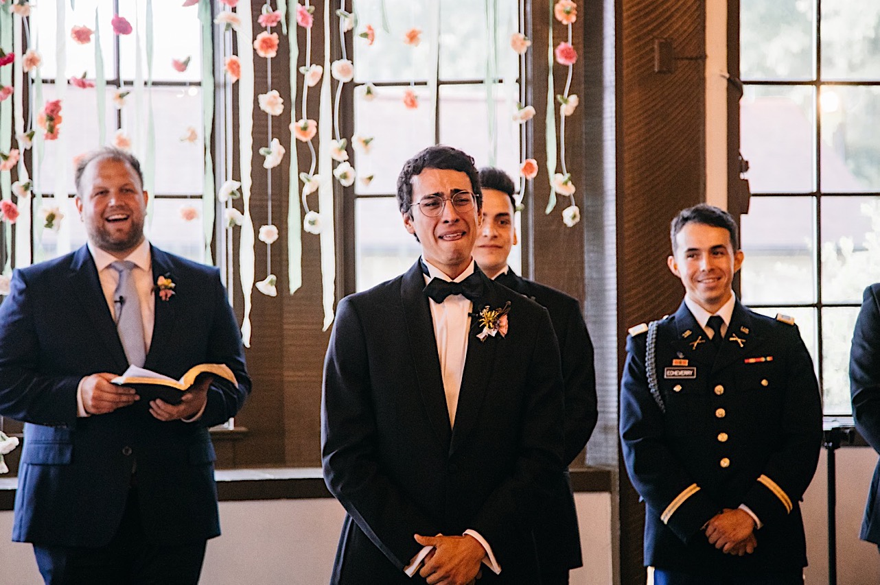 groom stands with officiant and groomsmen and cries when he sees bride