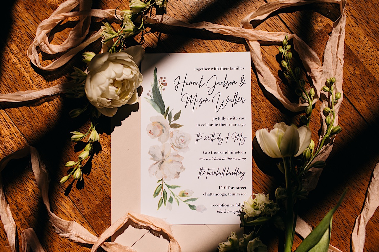 faded pink ribbons, white peony, and greens next to watercolor floral wedding invitation