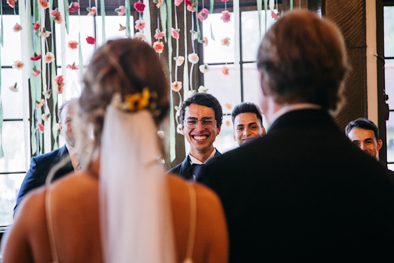 groom smiles when he sees bride and her father