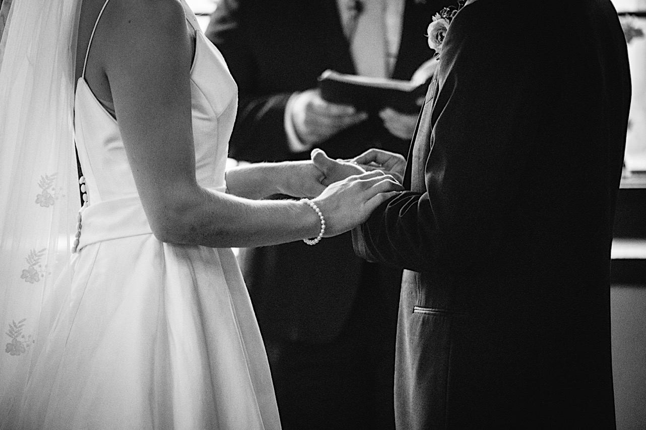 bride and groom hold hands in front of officiant
