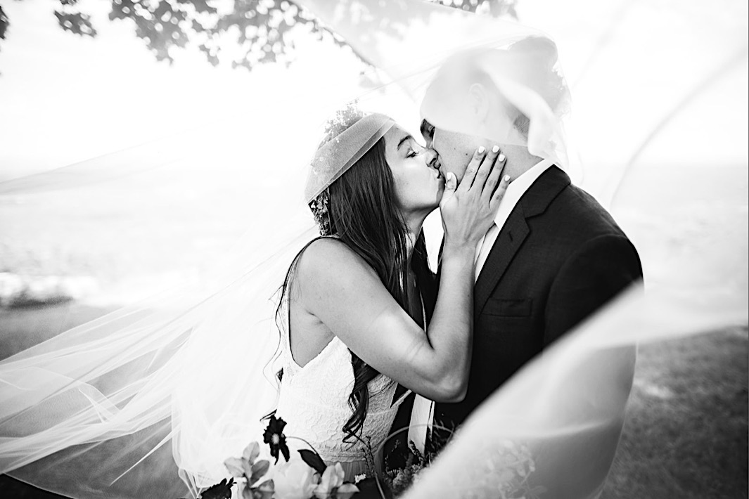 bride and groom kiss under her tulle veil