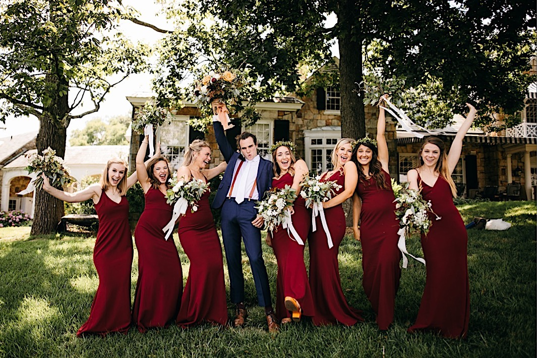 groom stands between bridesmaids holding and all lift Southerly Flower Farm bouquets into the air