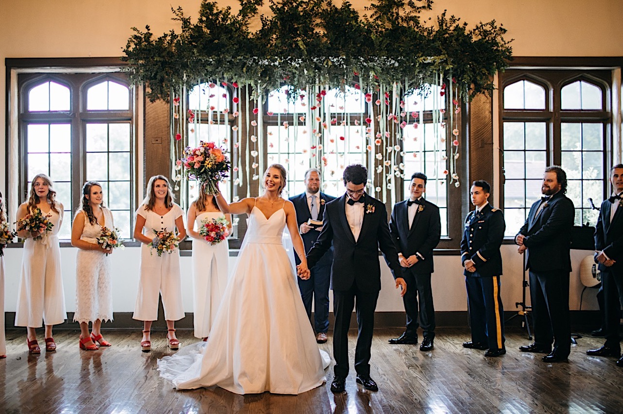 bride raises her Emily Kaye Designs bouquet as she and groom turn to face their guests