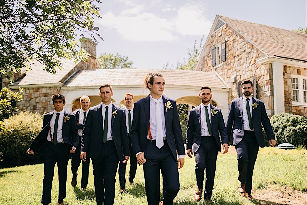 groom and groomsmen walk across a green lawn in front of a stone house on Lookout Mountain