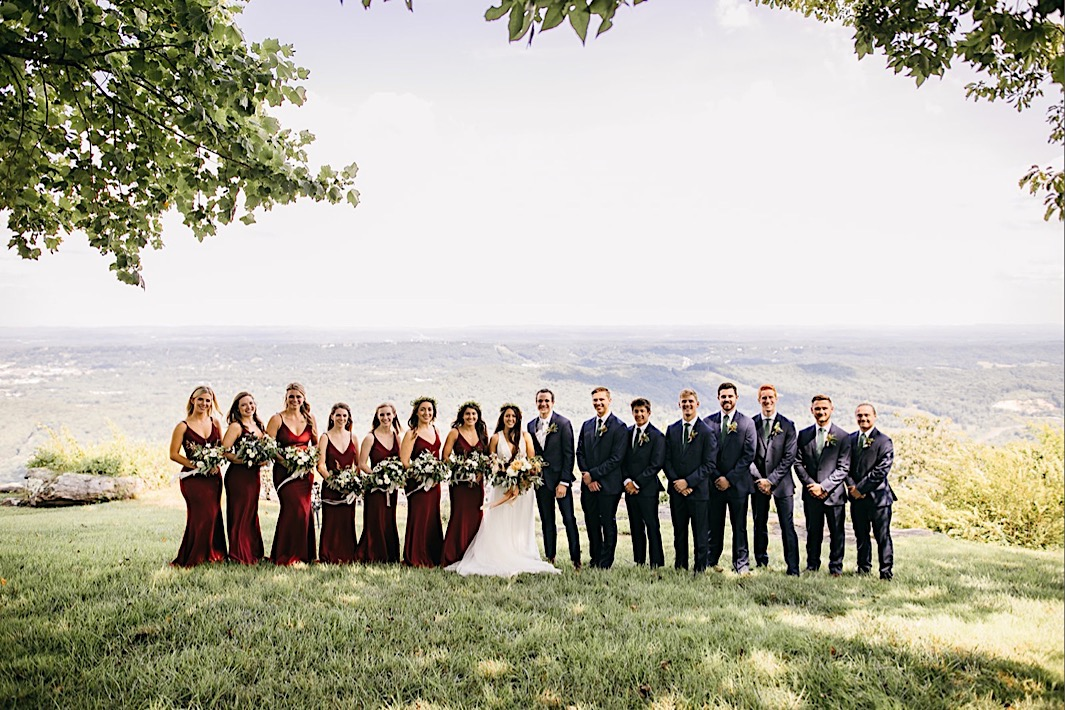 wedding party stands in a line in a grassy field on Lookout Mountain bluff overlooking Tennessee Valley