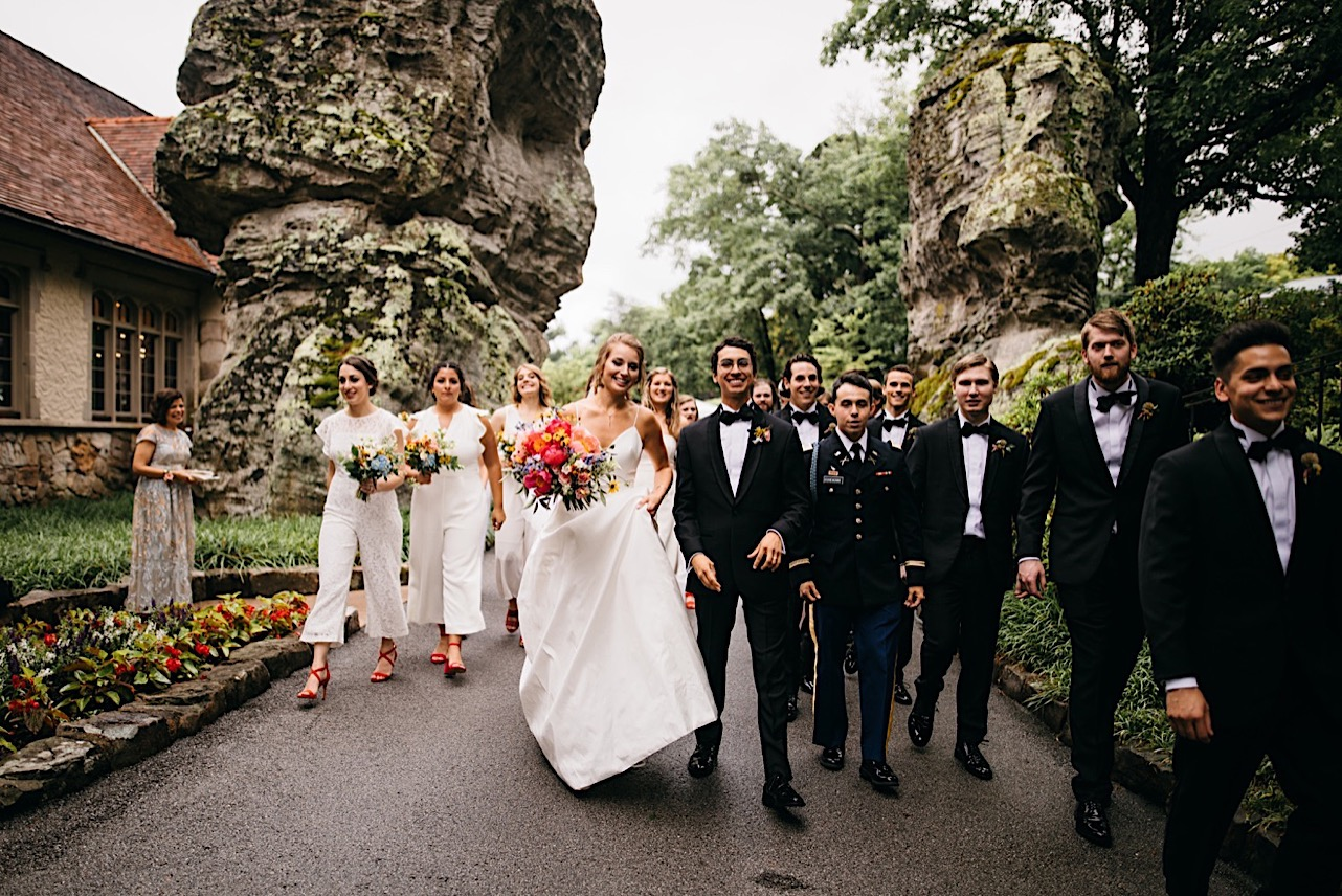 bride and groom and wedding party walk between large rock formations at the Lookout Mountain Club on Lookout Mountain Georgia
