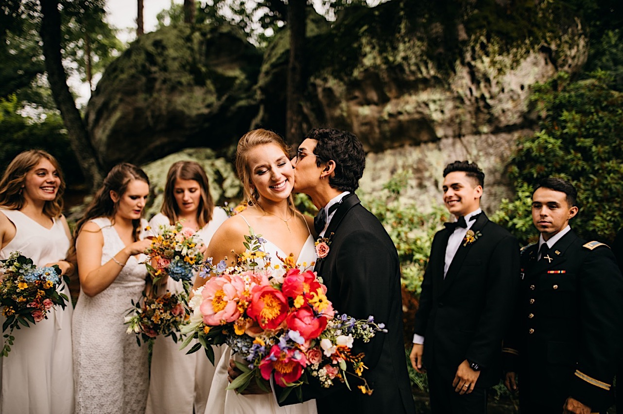 bride holds enormous colorful floral bouquet by Emily Kaye Designs while groom kisses her cheek and wedding party watches