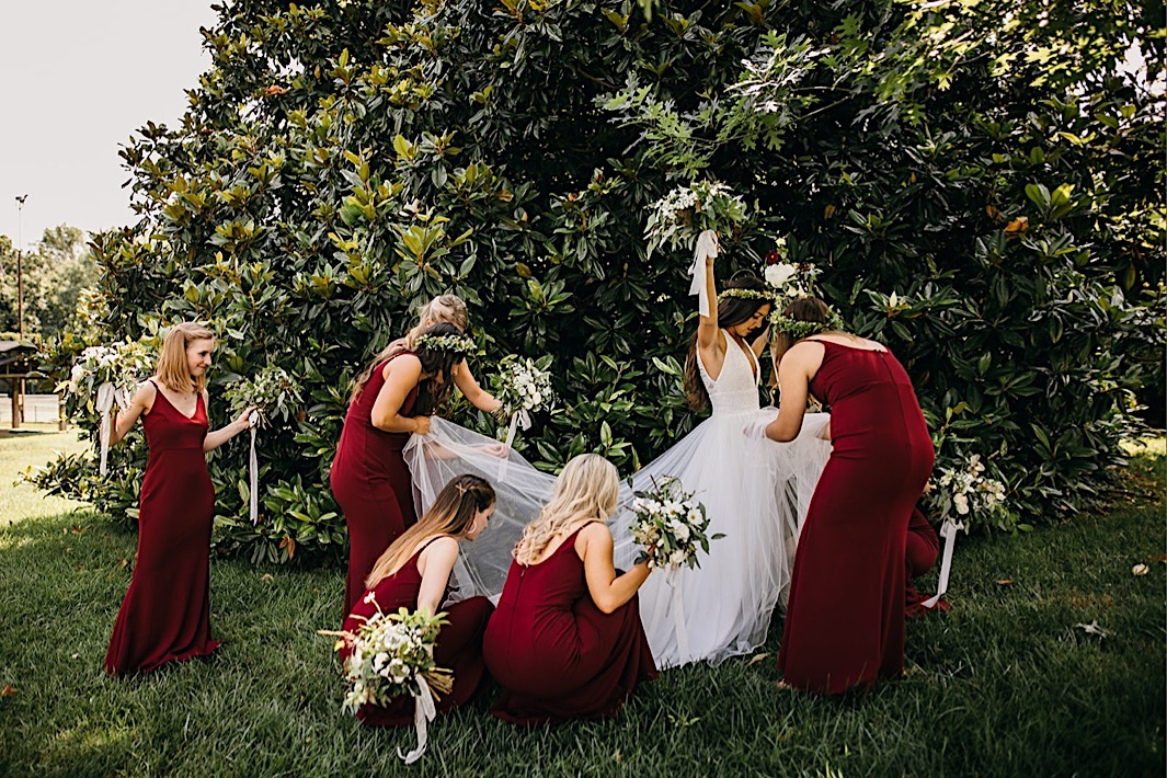 bridesmaids adjust bride's tulle gown in front of a magnolia tree as she holds her Southerly Flower Farm wedding bouquet high overhead