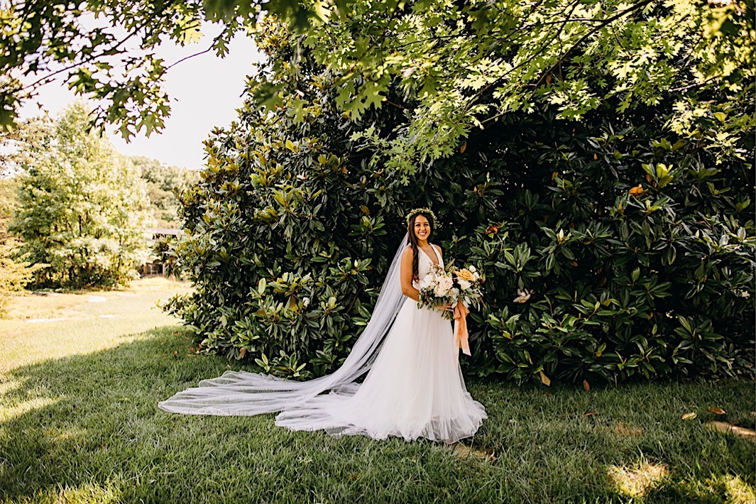 bride stands in front of a giant Magnolia tree holding her large Southerly Flower Farm bouquet with her long veil resting in the grass behind her