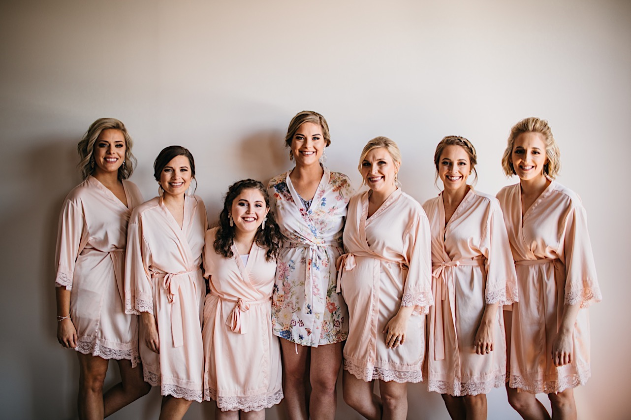 bride and bridesmaids standing against a white wall in silky, pink, knee-length bathrobes
