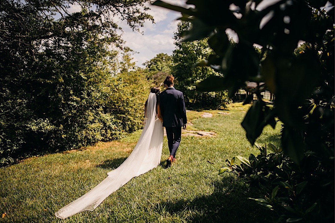 bride and groom hold hands and walk through a sunny lawn with her dress train and veil trailing behind her