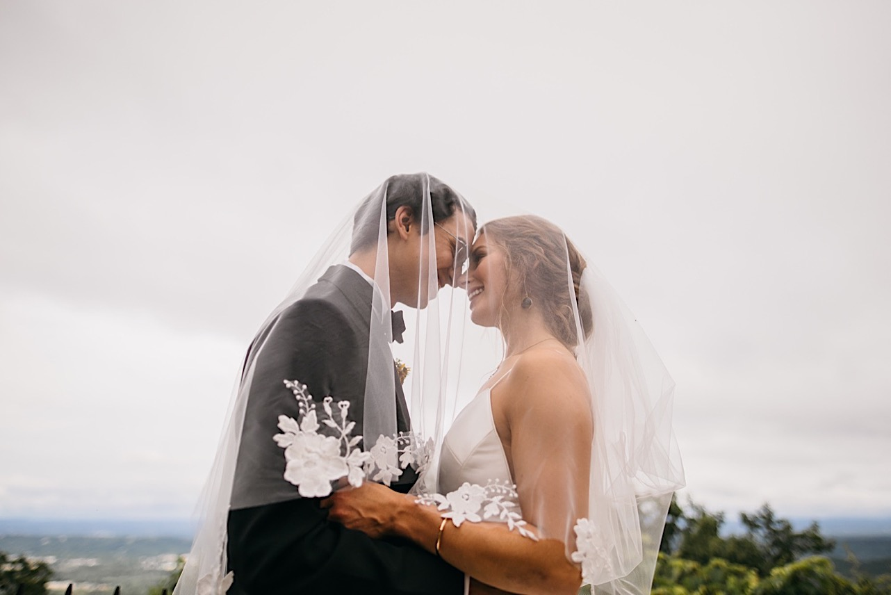 bride and groom touch noses under her veil