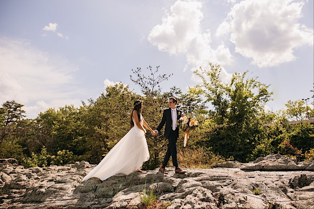 groom holds bride's large Southerly Flower Farm and her hand as they walk across a large boulder
