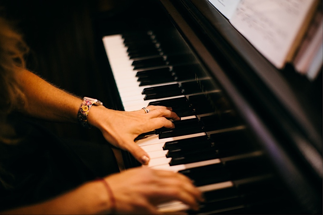 woman's hands playing a piano