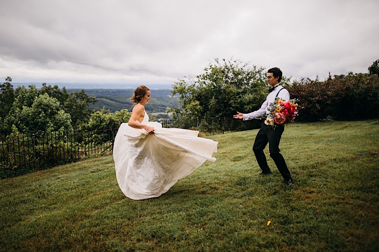 groom holds Emily Kaye Designs bright bouquet while bride twirls barefoot on the lawn