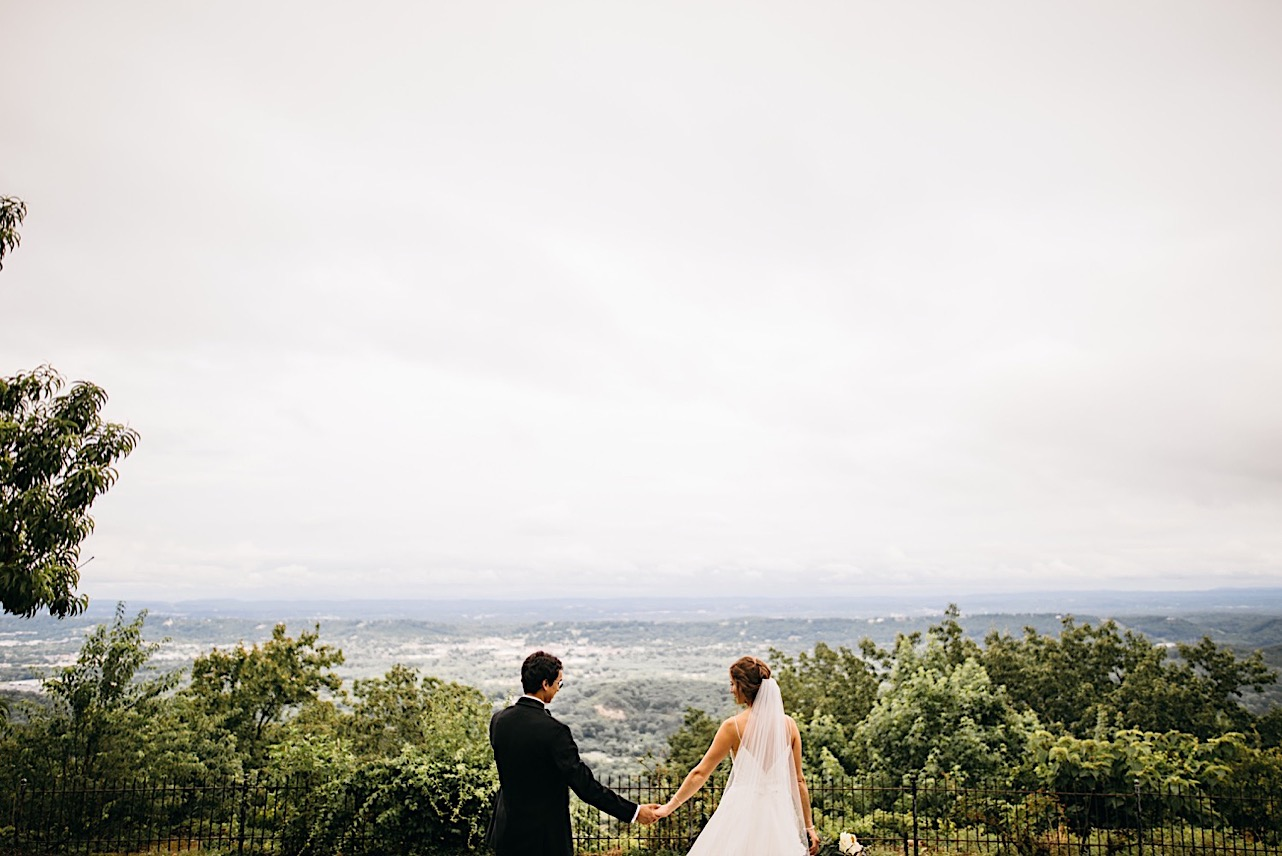 bride and groom hold hands in front of black iron fence on Lookout Mountain and overlook the rolling hills of the Tennessee Valley