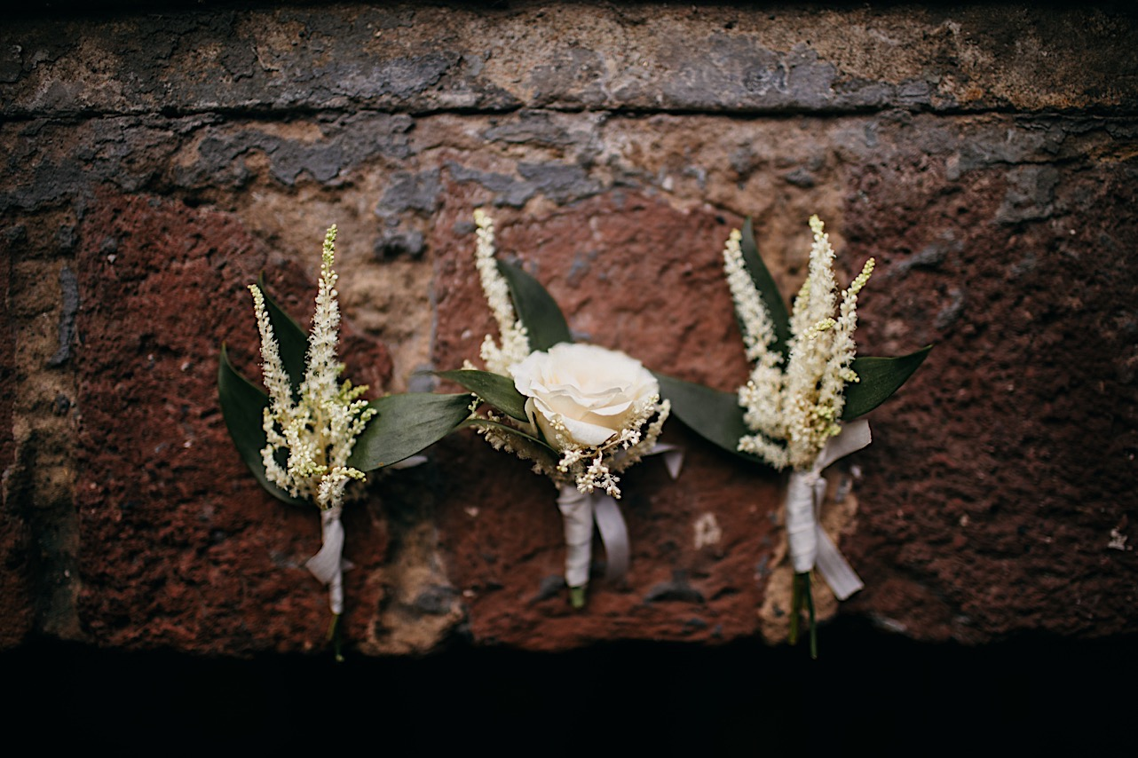 simple boutonnieres with white flowers and green leaves sit on a worn brick step