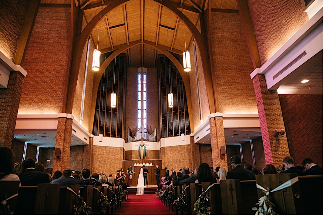 bride and groom stand at the altar of First Baptist Church in Chattanooga, TN