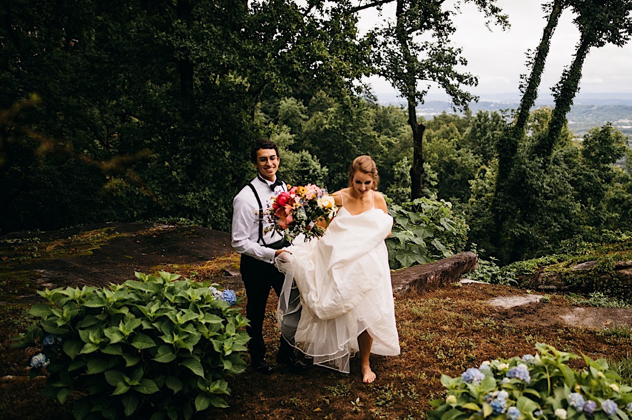 groom in shirt sleeves and suspenders carries brides train as she walks barefoot through Lookout Mountain garden with herEmily Kaye Designs bouquet
