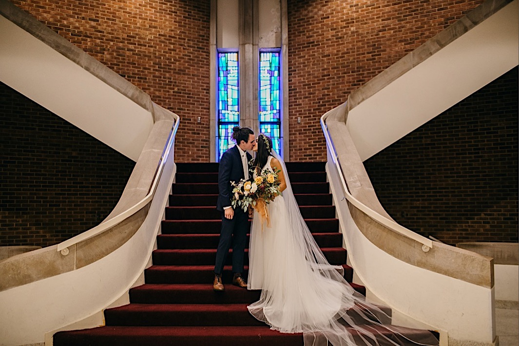 bride and groom kiss on a wide, red-carpeted stairway with her Southerly Flower Farm bouquet between them and her tulle gown and veil trailing down the stairs