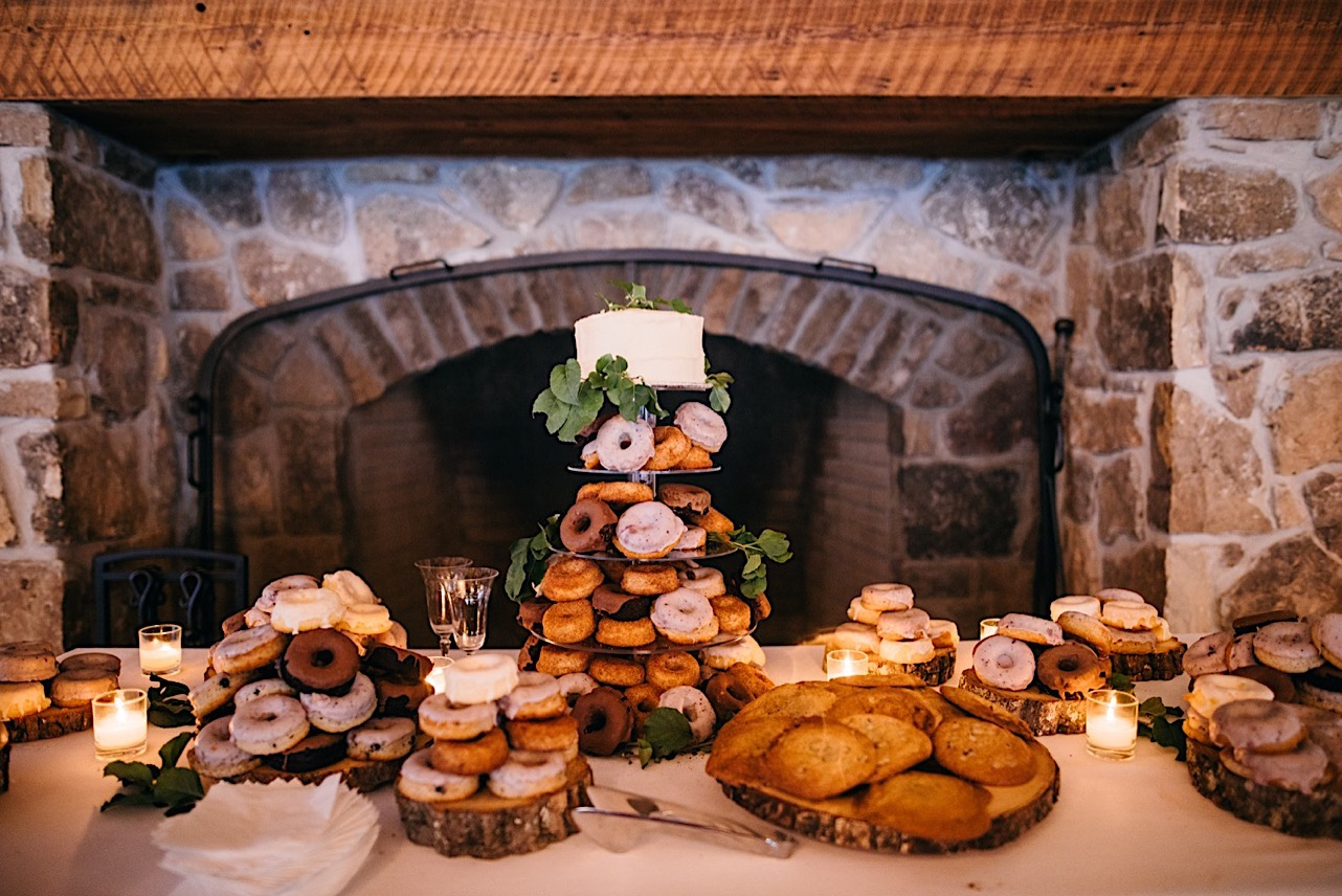 dessert table with cake tower holding variety of donuts on each layer topped by a small layer cake