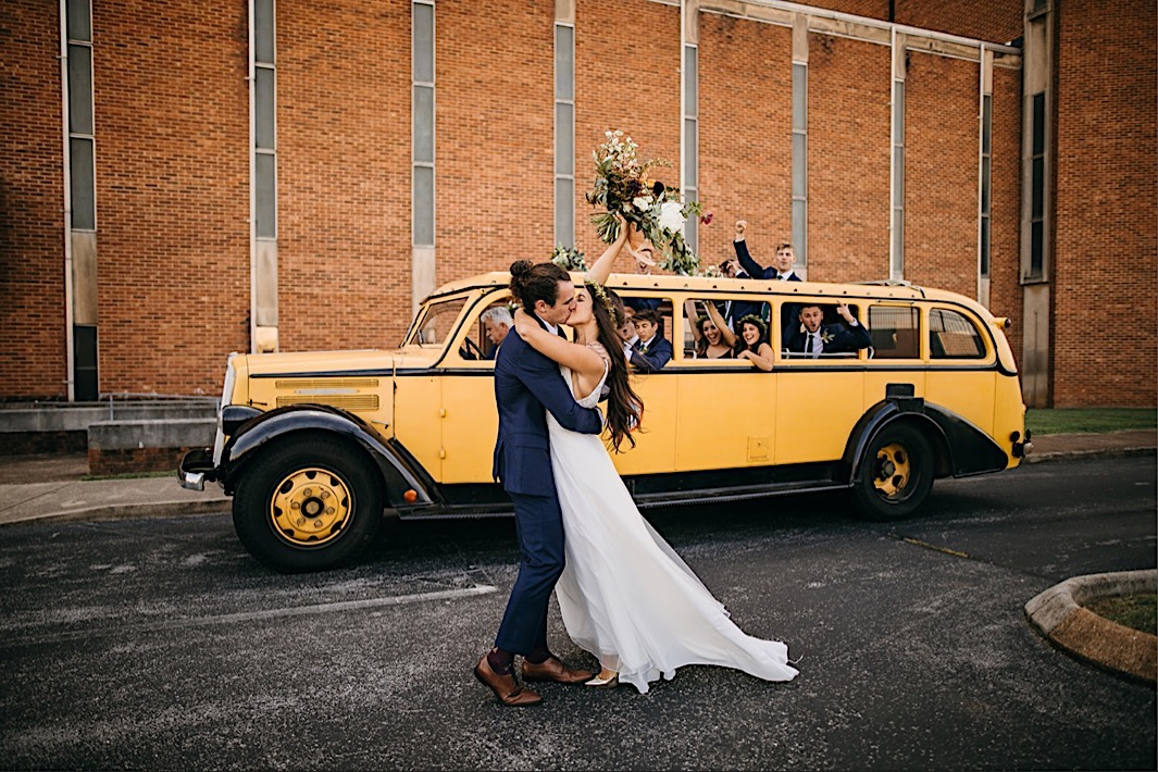 bride raises her Southerly Flower Farm bouquet in the air as groom kisses her in front of a vintage convertible bus