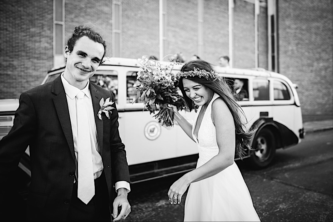 bride and groom laugh in front of a vintage convertible bus