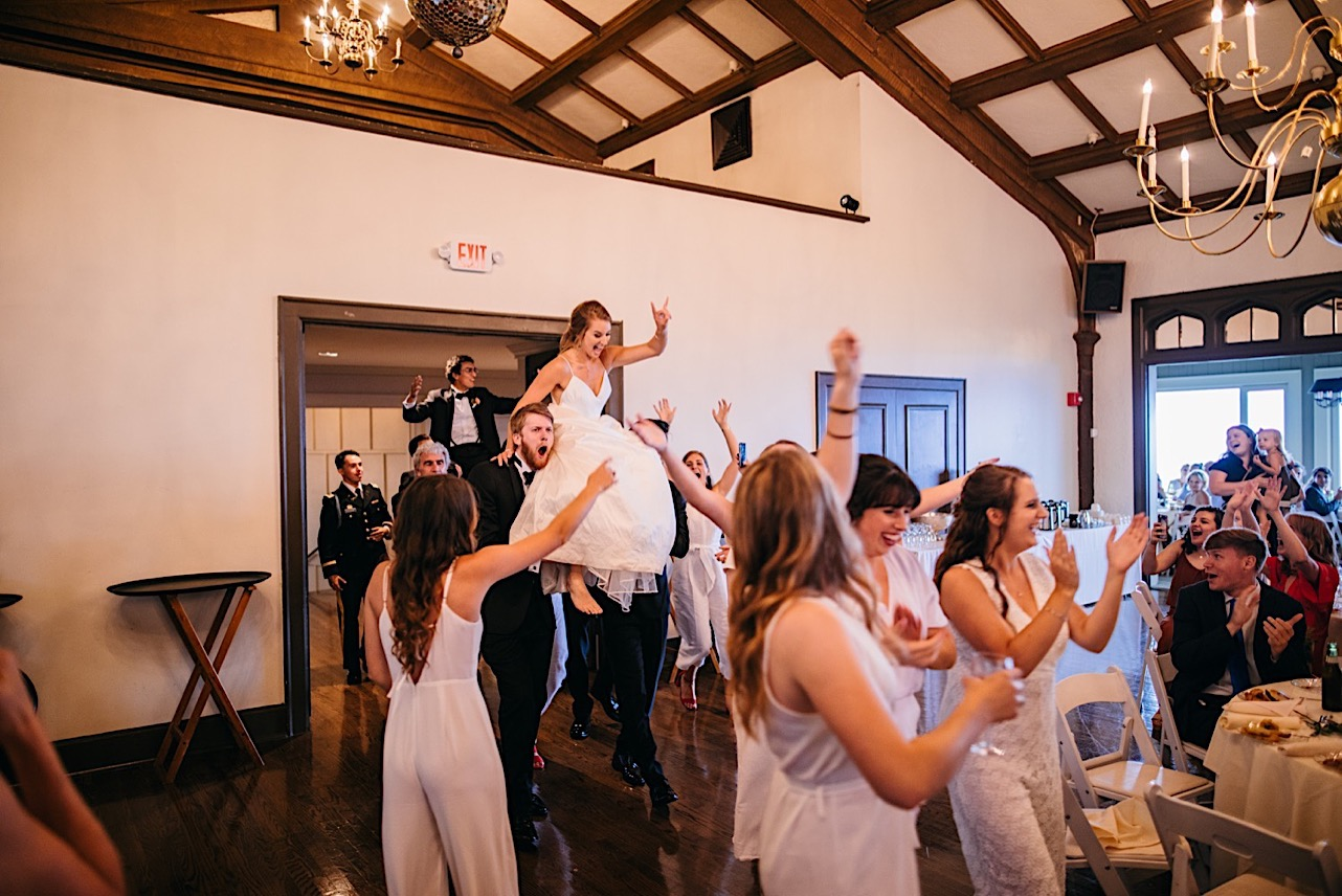 groomsmen carry bride on their shoulders and enter reception to cheering wedding guests