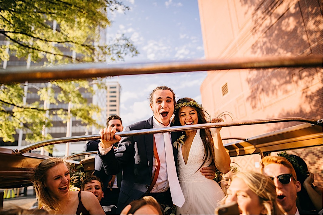 bride and groom stand through the roof of a convertible bus while they and bridal party laugh