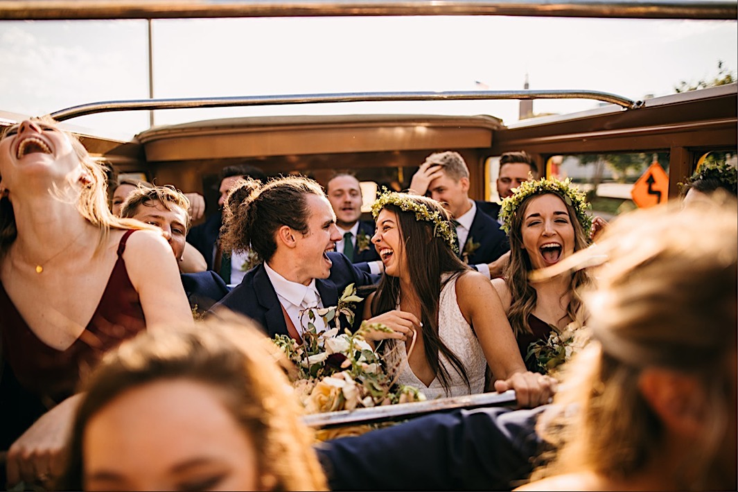 bride and groom laugh with each other and bridal party in a convertible bus