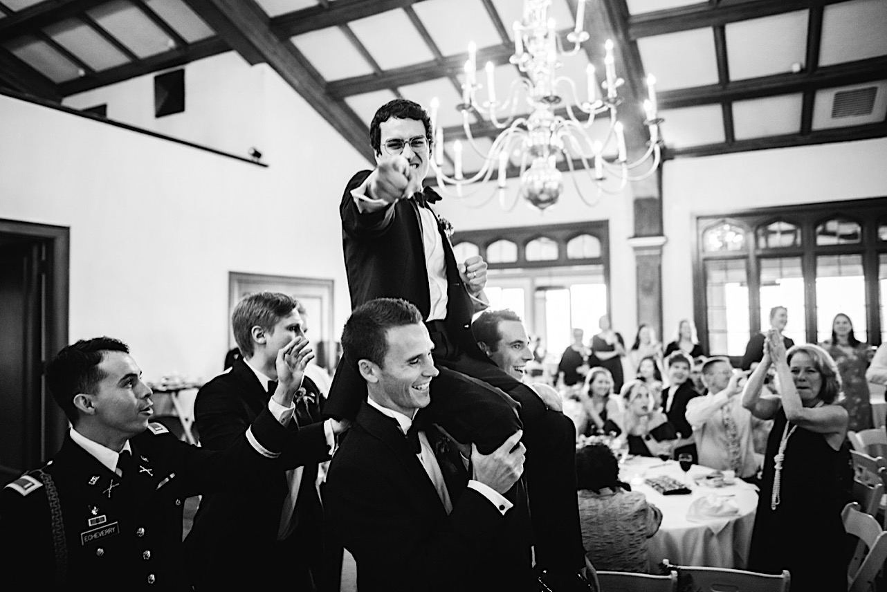 groomsmen carry groom on their shoulders and enter reception to cheering wedding guests