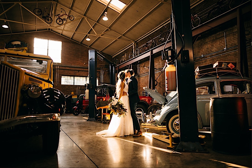 bride and groom kiss next to vintage cars in Chattanooga Tennessee