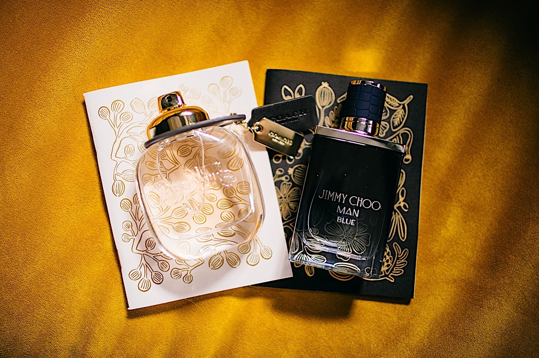 Bride and groom's perfume and cologne lay on top of their matching invites