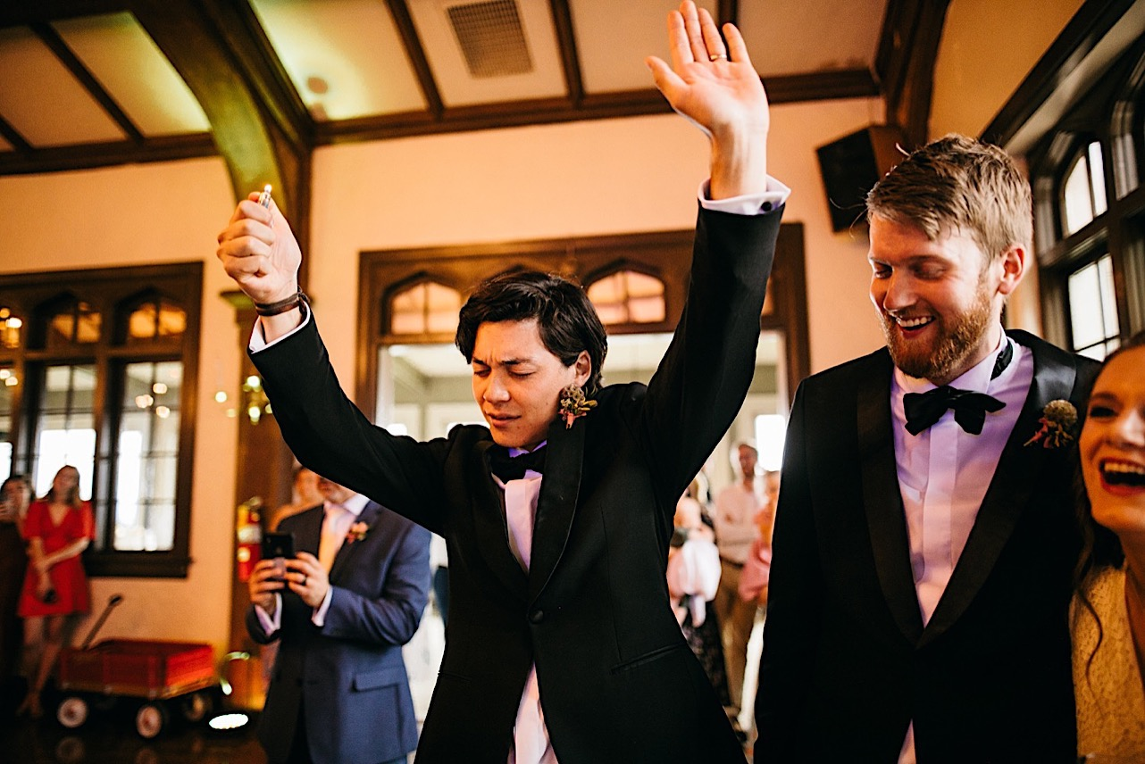 groomsmen laugh and raise lighters and hands during dance