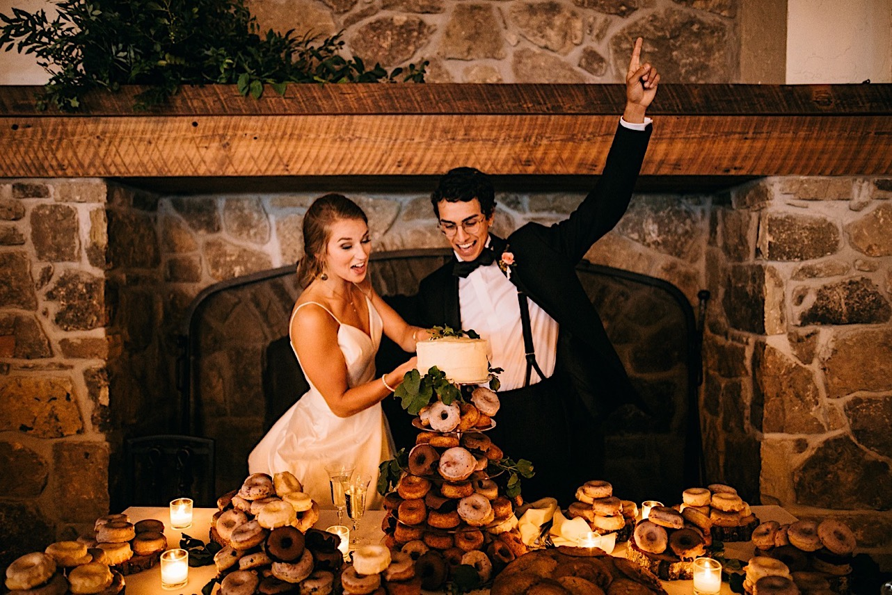 broom and bride cheer and he raises his hand in the air while they cut their cake in front of a large stone fireplace