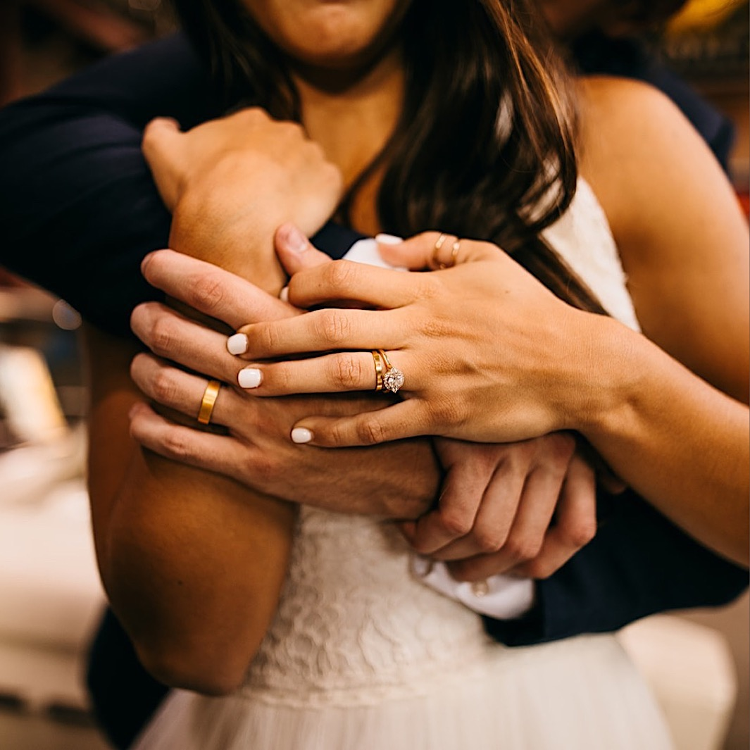 closeup of bride and groom rings as he hugs her over her shoulders