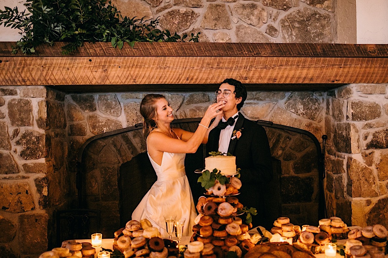 bride smiles while she feeds cake to groom in front of large stone fireplace at Lookout Mountain Club